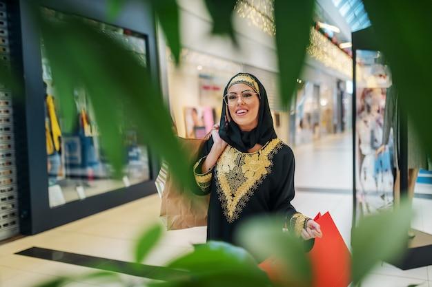 Prachtige lachende jonge arabische vrouw in traditionele slijtage staande in winkelcentrum met boodschappentassen in handen