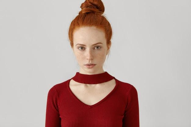 Prachtige luxe blanke roodharige vrouw met haarbroodje en sproeten, gekleed in stijlvolle rode jurk