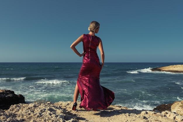 Prachtige mannequin in elegante rode jurk poseren op zee achtergrond.