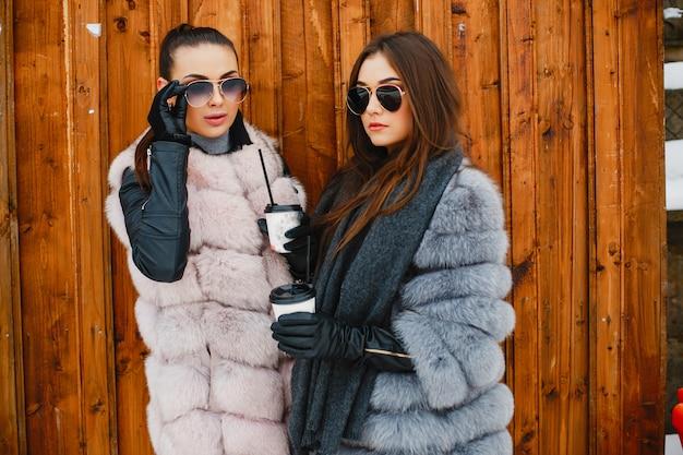 Prachtige meisjes in stijlvolle bontjassen staan in de buurt van bruine muur en drinken een koffie