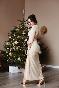 Prachtige modelvrouw met perfect lichaam in avondjurk in de woonkamer bij de kerstboom