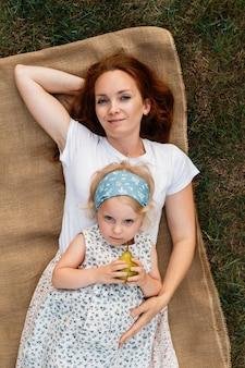 Prachtige moeder knuffelt haar dochtertje terwijl ze op haar ligt
