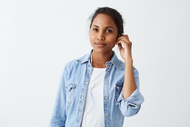 Prachtige mooie afro-amerikaanse vrouw met knotje, donkere ogen gekleed in wit t-shirt, blauwe jas, oortelefoon aan, muziek luisteren, muziekapp gebruiken op haar mobiele telefoon.