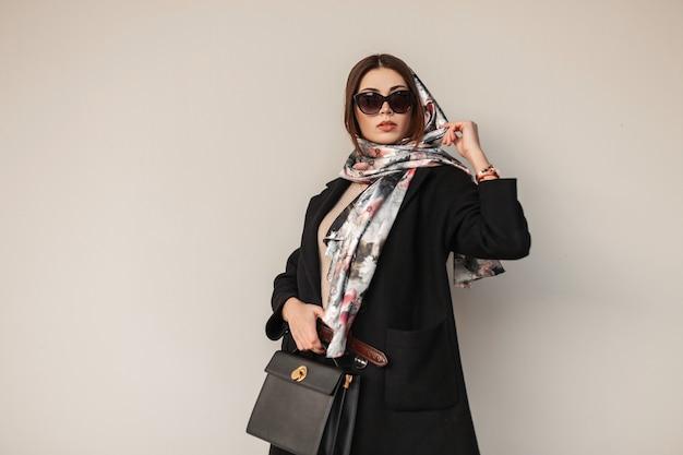 Prachtige mooie jonge professionele vrouw in stijlvolle zonnebril in trendy zwarte jas met leren tas met een vintage sjaal op hoofd poseren in de buurt van een muur buiten. aantrekkelijk meisje mannequin. sexy dame