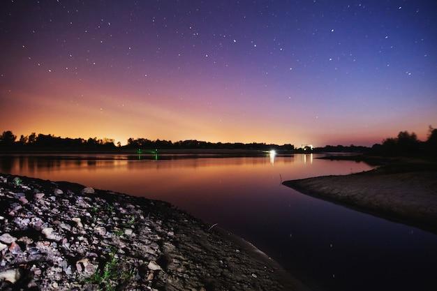 Prachtige nacht sterrenhemel landschap. sterren weerspiegeld in het water. astrofotografie. heldere sterrenhemel. lange sluitertijd. de spectaculaire lucht.