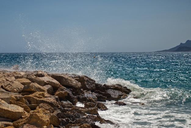 Prachtige oceaangolven komen naar de rotsachtige kusten die in cannes zijn vastgelegd