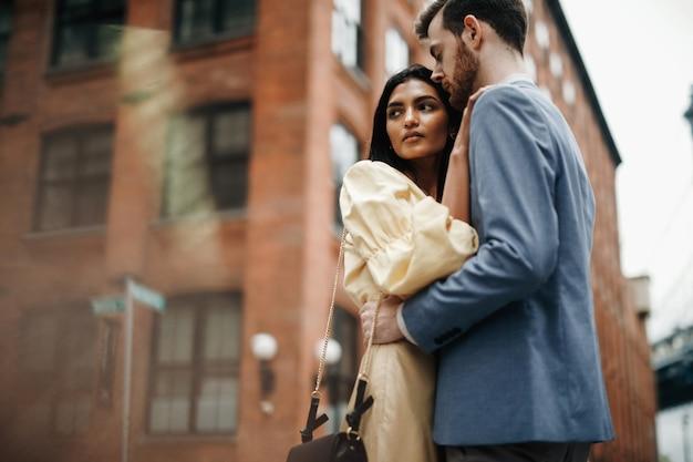 Prachtige paar amerikaanse man met baard en tedere oost-vrouw omhelzen elkaar
