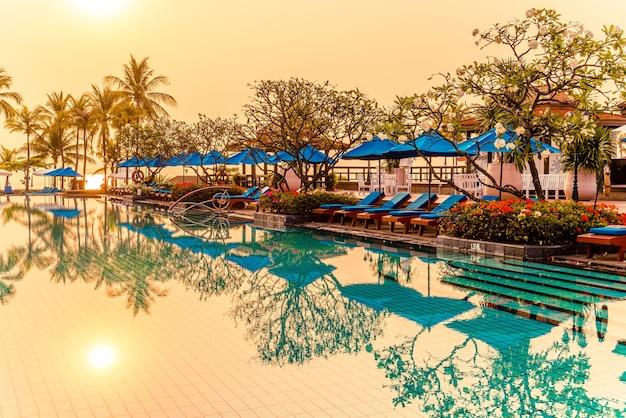 Prachtige palmboom met parasolstoel zwembad in luxe hotelresort bij zonsopgang. vakantie en vakantie concept