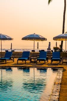 Prachtige palmboom met parasolstoel zwembad in luxe hotelresort bij zonsopgang