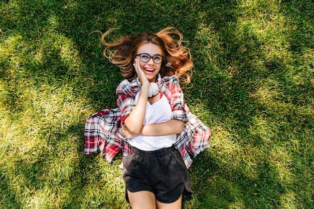 Prachtige peinzende vrouw liggend op zacht groen gras. overhead portret van geïnspireerd europees meisje met blij gezicht expressie.