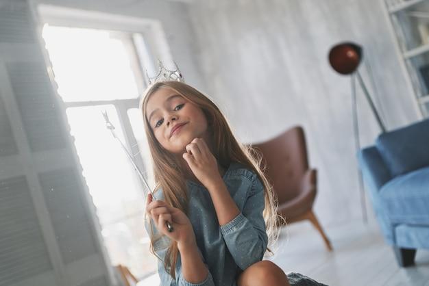 Prachtige prinses. trots klein meisje dat haar hand op haar kin houdt en met een toverstaf speelt terwijl ze thuis tijd doorbrengt