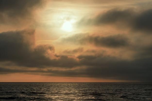 Prachtige rode zonsondergang, donkere wolken en de atlantische oceaan aan de horizon