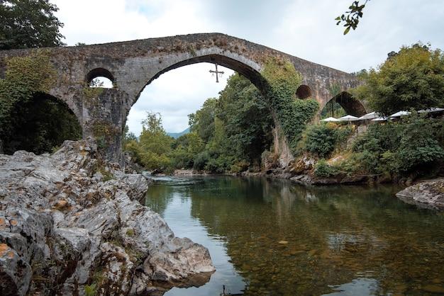 Prachtige romeinse brug gelegen in cangas de onis asturië naast de rivier de sella op een zomerse dag