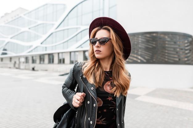 Prachtige roodharige hipster jonge vrouw in donkere zonnebril in een elegante hoed in een stijlvol zwart leren jasje