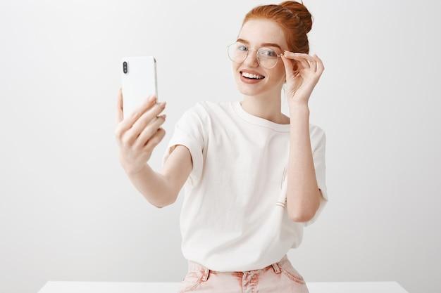 Prachtige roodharige vrouw die selfie met een bril
