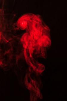 Prachtige rook van rode rook verspreid over zwarte achtergrond