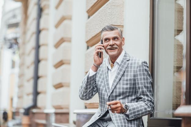 Prachtige senior man die telefonisch met iemand praat en op het terras zit