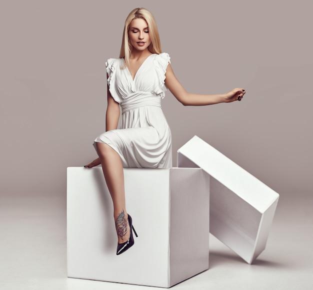 Prachtige sensuele blondevrouw in witte kleding in een grote het winkelen doos