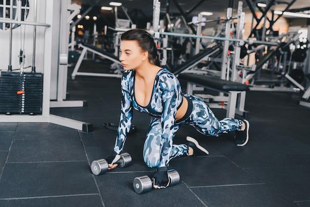 Prachtige sexy brunette die opwarmt en wat push-ups doet in de sportschool. atleet bouwer spieren levensstijl.