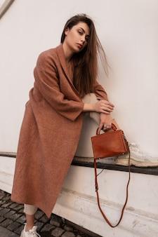 Prachtige sexy jonge vrouw met mooi haar in modieuze lange jas met bruine stijlvolle lederen handtas rust in de buurt van vintage witte muur op straat. mooi meisjesmodel in trendy kleding buitenshuis.