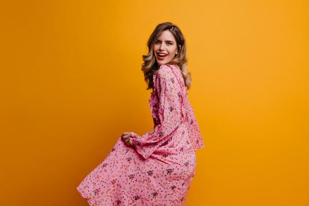 Prachtige slanke vrouw speelt met haar roze jurk. binnen schot van geïnspireerd kaukasisch meisje dat op gele muur danst.