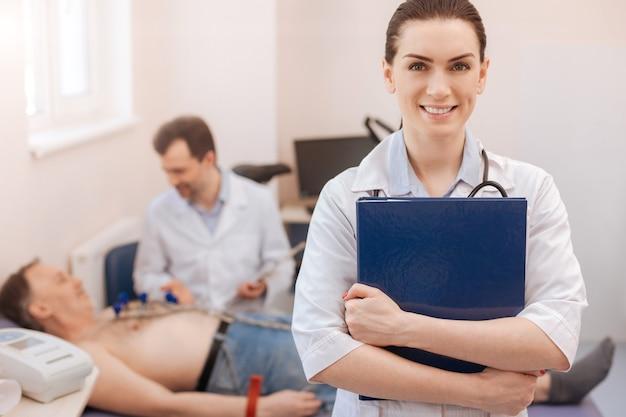 Prachtige, slimme, gekwalificeerde arts die het klinische dossier van de patiënt vasthoudt en er verrukt uitziet na een consult samen met haar collega