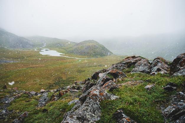 Prachtige sneeuwval in de bergen. sfeervol groen alpenlandschap met grote sneeuwvlokken. klein meertje, waterstromen en rotsachtige heuvel met scherpe steile stenen tijdens sneeuwval. sneeuwvlokken in hoogland