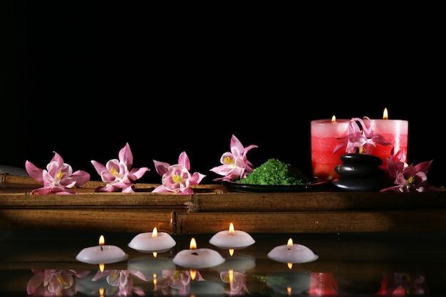 Prachtige spa-compositie met bloemen en kaarsen op zwarte achtergrond