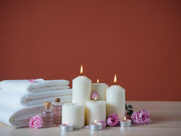 Prachtige spa-compositie met brandende geurkaarsen en aroma-olie, roze rozen op houten tafel