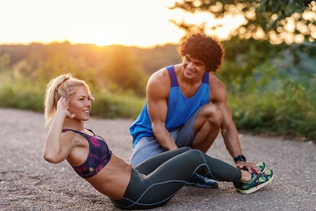 Prachtige sportieve blonde vrouw met paardenstaart crunches terwijl haar vriendje haar benen vasthoudt en haar helpt. landelijke scène, zonnige zomerdag.