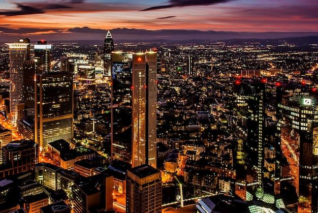 Prachtige stad met hoge wolkenkrabbers die 's nachts onder de kleurrijke lucht glinsteren