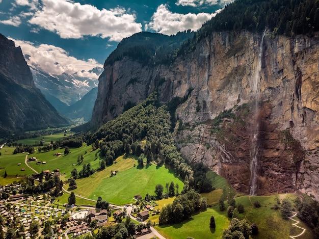 Prachtige staubbachfall-waterval stroomt door de pittoreske lauterbrunnen-vallei en het dorp in het kanton bern