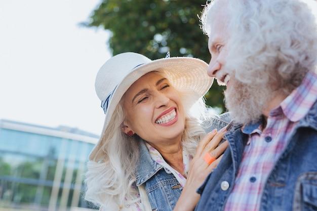 Prachtige stijl. positieve opgetogen vrouw die een hoed draagt terwijl ze naar haar man kijkt