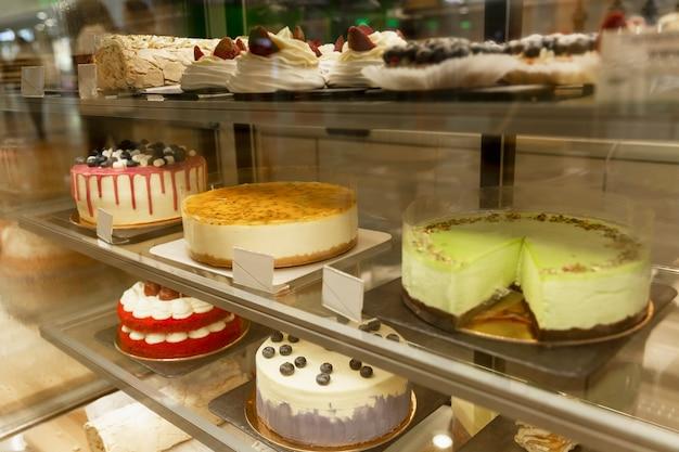 Prachtige taarten en gebakjes om van te watertanden op een glazen vitrine. detailopname.