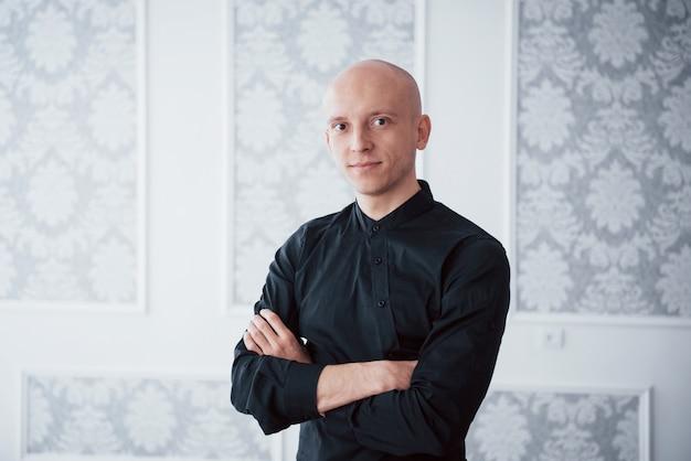 Prachtige verlichting. portret van vrolijke man in de klassieke zwarte shirt met gekruiste armen