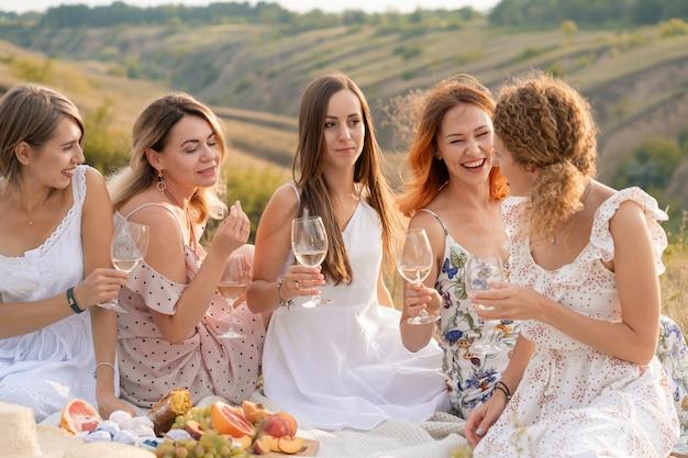 Prachtige vriendinnen hebben plezier, drinken wijn en genieten van heuvels, landschapspicknick