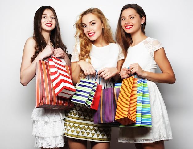 Prachtige vriendinnen met boodschappentassen poseren