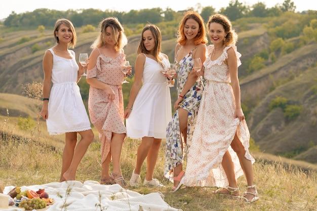 Prachtige vriendinnen plezier hebben en geniet van een zomer groene hlls picknick, dansen en alcohol drinken. mensen concept.