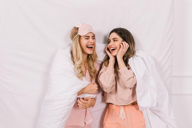 Prachtige vriendinnen praten in bed