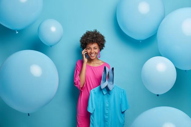 Prachtige vrolijke donkere vrouw geniet van telefoongesprek met beste vriend, probeert nieuwe schoenen met hoge hakken en shirt op hanger, bereidt zich voor op vrijgezellenfeest, vormt tegen blauwe muur