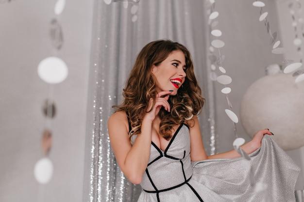 Prachtige, vrolijke langharige vrouw verheugt zich op vakantie op nieuwjaarsfeest. portret van een vrouw die haar schitterende zilveren jurk speelt
