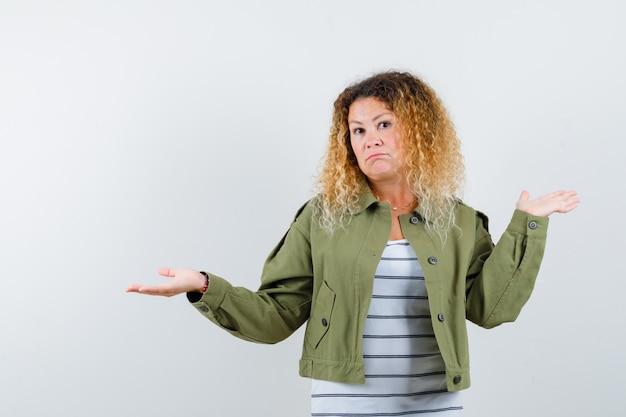 Prachtige vrouw die hulpeloos gebaar in groen jasje, overhemd toont en onbeslist, vooraanzicht kijkt.