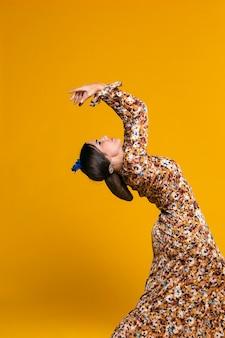 Prachtige vrouw die terug met oranje achtergrond buigt