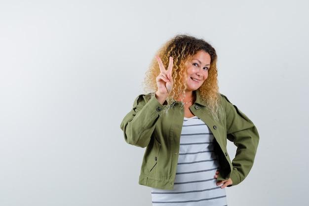 Prachtige vrouw die v-teken in groen jasje, overhemd toont en vrolijk kijkt. vooraanzicht.