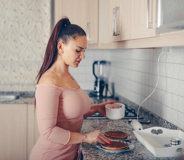 Prachtige vrouw gieten gemengde aardbei op pannenkoeken in de keuken in zalm roze crop top en broek
