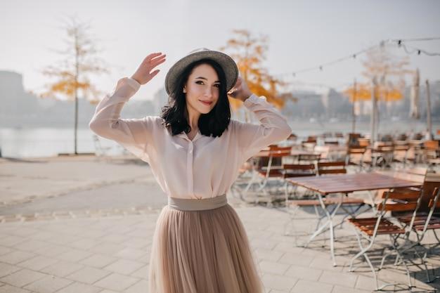 Prachtige vrouw in blouse en rok dansen op onscherpte