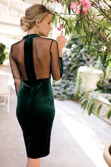 Prachtige vrouw in de groene cocktailjurk die bij de palmboom staat, dun, mode, kapsel, glamoureus, schoenen, buiten, perfect lichaam, blond, schoonheid, bedenken, rug