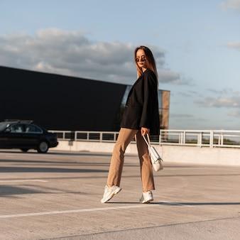 Prachtige vrouw in fashion zonnebril in elegante stijlvolle kleding in trendy sneakers met vintage tas poses op asfalt tegen blauwe zonnige hemel. stijlvol vrij stedelijk meisjesmodel in jeugdkleren in stad.