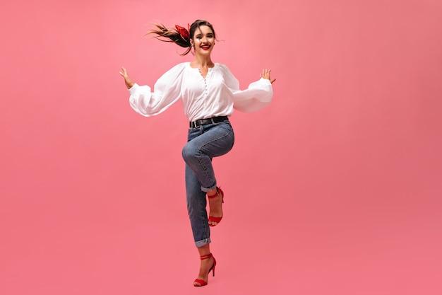 Prachtige vrouw in goed humeur dansen op roze achtergrond. glimlachende dame in blouse met wijde mouwen en rode schoenen die zich voordeed op geïsoleerde achtergrond.