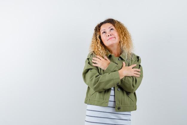 Prachtige vrouw in groen jasje, overhemd knuffelt zichzelf en kijkt bezorgd, vooraanzicht.